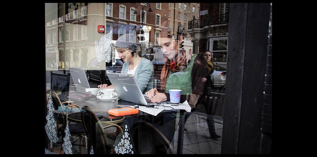 Amrai und Caterina in einem Londoner Café bei der digitalen Arbeit